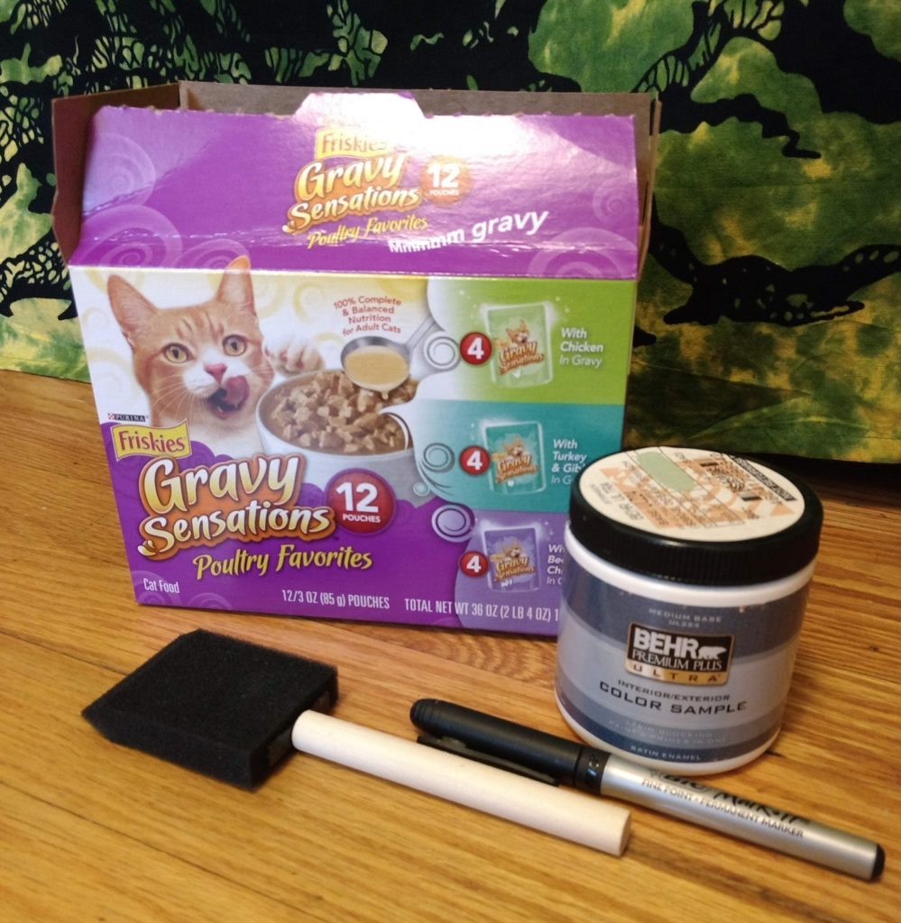 Friskies box with paint and paintbrush