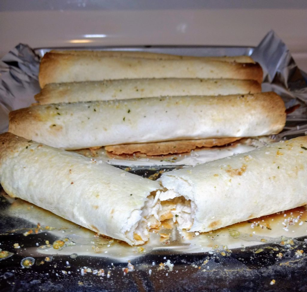 baked chicken taquitos broken in half with a creamy middle