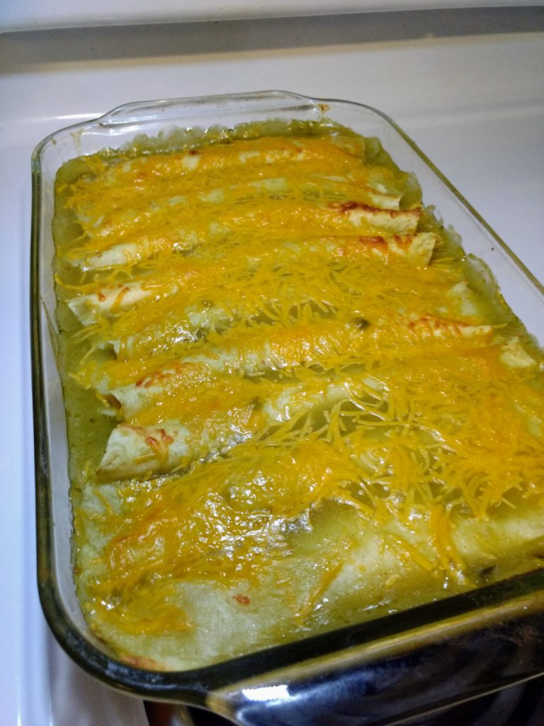 creamy baked green chili chicken enchiladas in pan